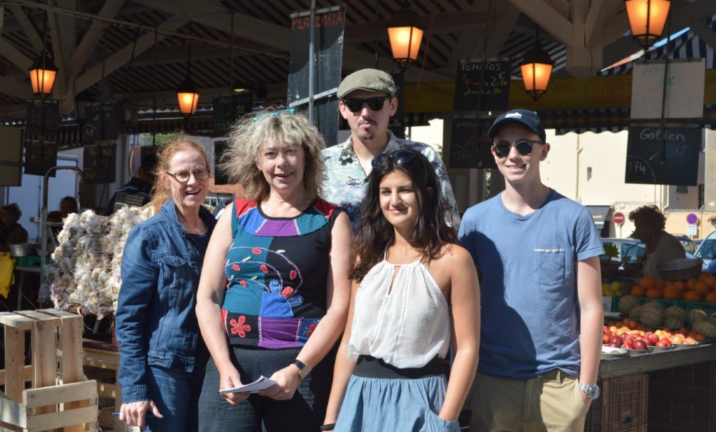 A group of adult students on a class activity at the market place during their French language course in France