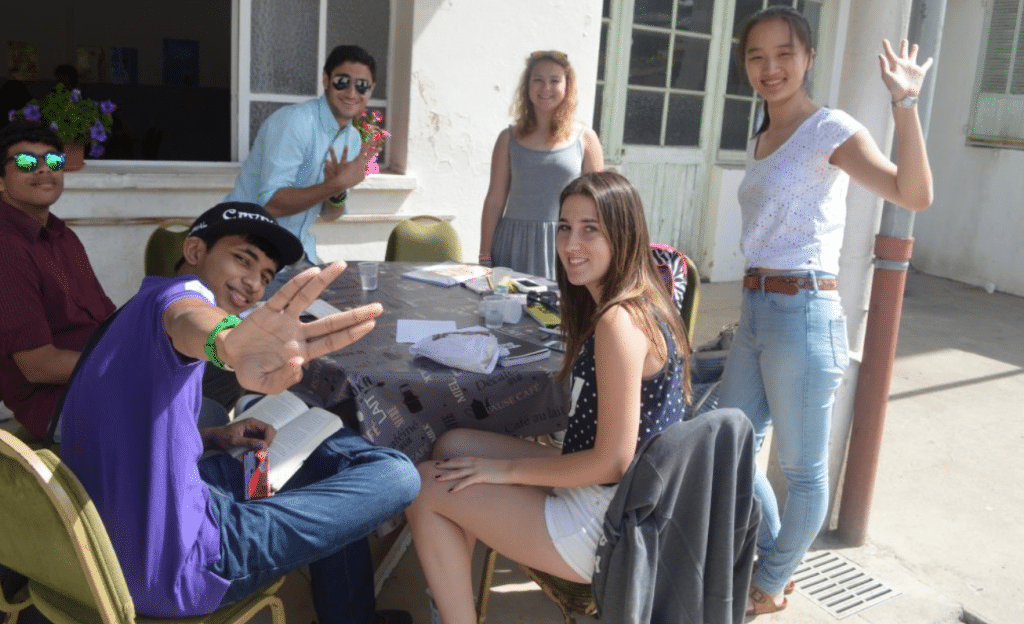 A group of teenager students gather at the school break and make new friends during their French language stay in France